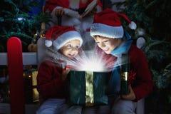 Duas crianças que abrem o presente do Natal Imagens de Stock