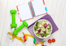 Dumbells, tape measure, healthy food and notepad for copy space Stock Images