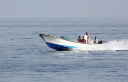 Early morning fisher men moving in sea on speedboat Stock Photos
