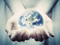 The earth shines in young woman hands. Save the world Royalty Free Stock Images