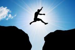 El hombre que salta sobre precipicio Riesgo, desafío, éxito Fotografía de archivo libre de regalías