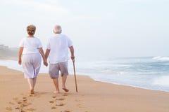 Elderly couple walking on beach Royalty Free Stock Image