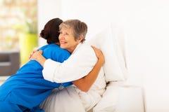 Elderly hugging caregiver Royalty Free Stock Image