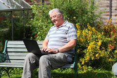 An elderly man with laptop outside. Royalty Free Stock Images