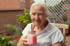 Elderly woman with smoothie Stock Photography