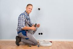 Electrician stripping wire in house Royalty Free Stock Photography