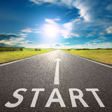 Empty asphalt road with a sign start against sun Stock Image