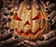 Evil pumpkin with glowing eyes that are holding Royalty Free Stock Images