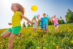 Excited kids with balloons run in field Stock Image