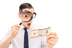 Excited man looking at dollar bill with magnifier Stock Photography