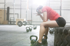 Exhausted woman sitting on tire in crossfit gym Royalty Free Stock Image
