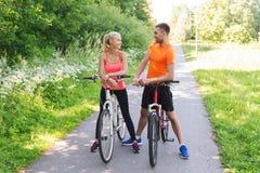 Fahrrad des glücklichen Paars Reitdraußen Stockbild