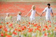 Famiglia che cammina attraverso il campo del papavero Fotografia Stock Libera da Diritti