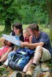 famiglia che fa un'escursione osservando programma Immagine Stock Libera da Diritti
