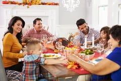 Familie met Grootouders die Dankzeggings van Maaltijd genieten bij Lijst Stock Afbeelding