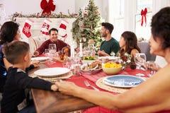 Familie met Grootouders die Grace Before Christmas Meal zeggen Stock Foto