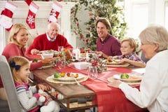 Familie met Grootouders die Kerstmis van Maaltijd genieten bij Lijst Stock Fotografie