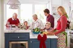 Familie met Grootouders die Kerstmismaaltijd in Keuken voorbereiden Stock Fotografie