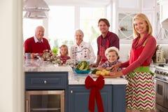 Familie met Grootouders die Kerstmismaaltijd in Keuken voorbereiden Stock Afbeeldingen