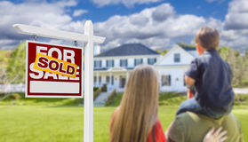 Family Facing Sold For Sale Real Estate Sign and House Stock Photography