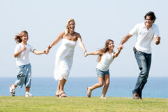 Family of four running on meadow Stock Images