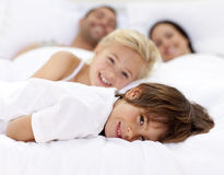 Family resting in parent's bed Stock Photos