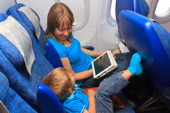 Family with touch pad in plane Stock Photography