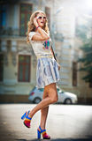 Fashion girl with short skirt , bag and high heels walking on street, sun glasses Stock Photo