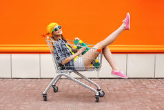 Fashion hipster cool girl with skateboard in shopping cart Royalty Free Stock Photo