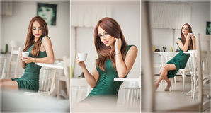 Fashionable attractive young woman in green dress sitting in restaurant. Beautiful redhead in elegant scenery with a cup of coffee Royalty Free Stock Photos