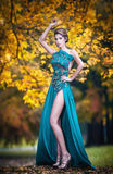 Fashionable beautiful young woman in blue dress posing outdoor rusty forest in background. Attractive girl with elegant dress Royalty Free Stock Images