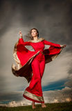 Fashionable beautiful young woman in red long dress posing outdoor with cloudy dramatic sky in background Stock Photography