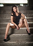 Fashionable pretty young woman with long legs sitting on old stone stairs. Beautiful long hair brunette on high heels shoes posing Royalty Free Stock Photo