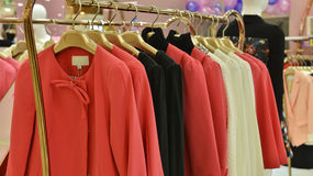 Fashionable women dress on hangers in clothing shop Stock Photography