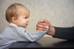 Father and kid arm wrestling competition Stock Images