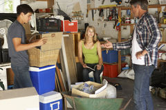 Father Organising Two Teenagers Clearing Garage For Yard Sale Stock Photography