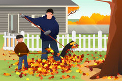 Father and Son Raking Leaves in the Yard During Fall Season Royalty Free Stock Photos