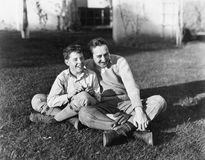 Father and son sitting together on the grass in the back yard Royalty Free Stock Photos