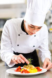 Female Chef in restaurant kitchen cooking Stock Image