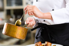 Female Chef in restaurant kitchen cooking Stock Photography
