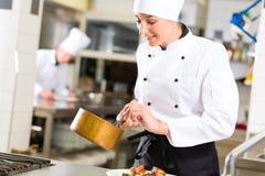 Female Chef in restaurant kitchen cooking Stock Photo