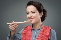 Female cook tasting a recipe Stock Photos