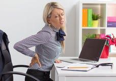 Femme ayant des douleurs de dos tout en se reposant au bureau dans le bureau Photo stock