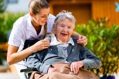 Femme supérieure dans la maison de repos avec l'infirmière dans le jardin Images stock