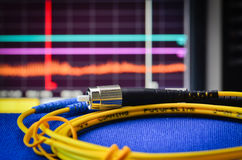 Fiberoptisches Kabel mit Spektrum analiser im Hintergrund Stockbild