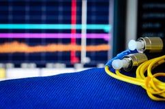 Fiberoptisches Kabel mit Spektrum analiser im Hintergrund Stockfotografie