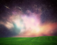Field of grass under dream galaxy sky, space, glowing stars. Stock Images