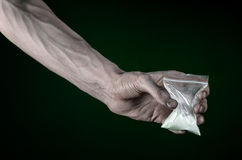 The fight against drugs and drug addiction topic: dirty hand holding a bag addict cocaine on a dark green background in the studio Stock Photography