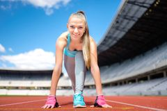 Fitness athletic girl preparing for a run on sport track at stadium.  Healthy and sporty lifestyle with young girl running Stock Images