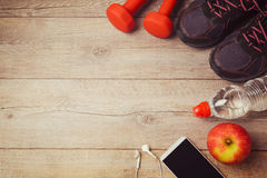 Fitness background with bottle of water, dumbbells and athletic shoes. View from above Royalty Free Stock Photos